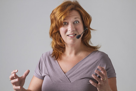 red hair female phone agent with headset with angry expression photo