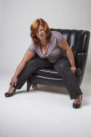 love seat: forty something woman with red hair sitting on a black leather love seat