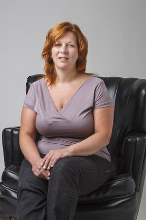 loveseat: woman in her forties with red hair sitting on a black leather love set