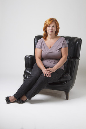 woman in her early forties with red hair sitting on a black leather love set