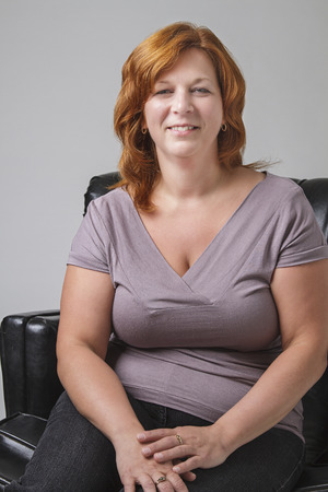 loveseat: forty something woman with red hair sitting on a black leather love seat