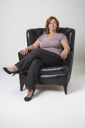 love seat: early forties woman with red hair sitting in a black leather love seat Stock Photo