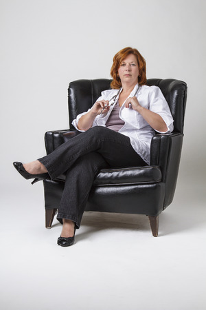 love seat: woman doctor seating in a black leather love seat with serious expression Stock Photo