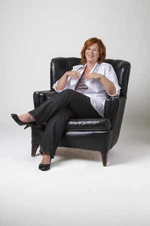 forty something: forty something doctor with red hair, with happy expression, sitting in a black leather love seat Stock Photo