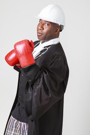 toga: Mediados de los a�os cuarenta hombre calvo negro que llevaba una toga abogado canadiense, casco blanco, estetoscopio y el boxeo guante de boxeo