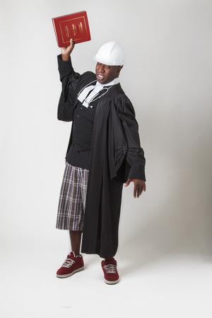 forty something: forty something bald black man wearing a lawyer toga, hard hat and a stethoscope, about the slam a bilingual law book to the ground Stock Photo