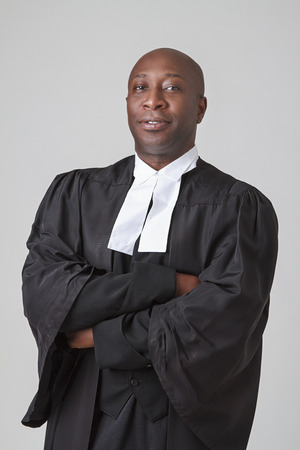 Bald black man, in his forties, wearing a judicial toga