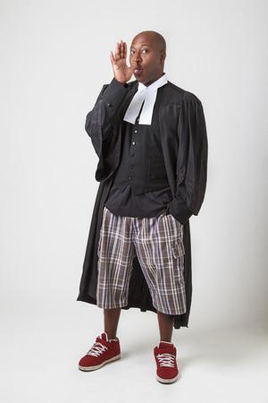 toga: Hombre negro calvo llevaba una toga judicial haciendo una cara mediante la extinci�n de su lengua y su pulgar en la nariz Foto de archivo