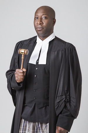 forty something: forty something, bald, african american wearing a canadian lawyer toga holding a gavel Stock Photo