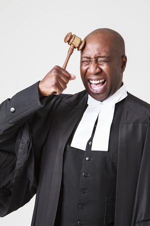 toga: african hombres calvas americanas vistiendo una toga abogado y golpeando su cabeza con un martillo