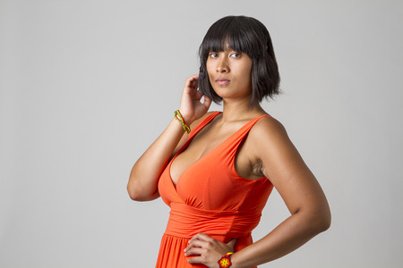 low cut: Philipino woman wearing a low cut orange dress and a headset Stock Photo