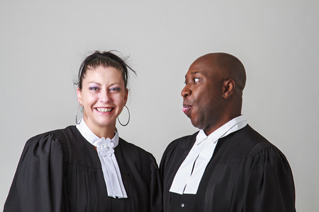 making a face: bald black man making a face to a woman, both wearing canadian lawyer toga