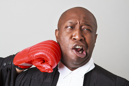 bald black man wearing canadian lawyer toga getting punch in the face by a red boxing glove photo