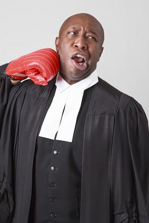 toga: Hombre negro calvo vistiendo toga abogado canadiense conseguir pu�etazo en la cara por un guante de boxeo rojo Foto de archivo