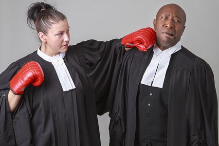 toga: caucasian woman wearing a lawyer toga punching a black man wearing a lawyer toga