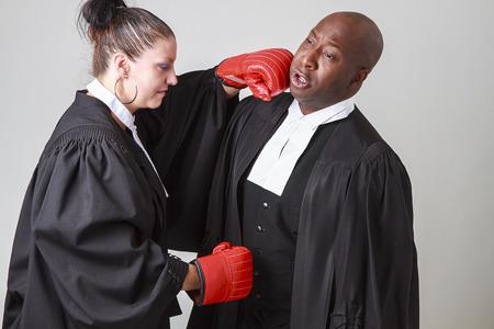 caucasian woman wearing a lawyer toga punching a black man wearing a lawyer toga photo