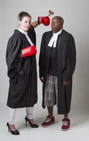 toga: Mujer golpeando a un hombre en la cabeza con un martillo, ambos vistiendo abogados canadienses toga Foto de archivo