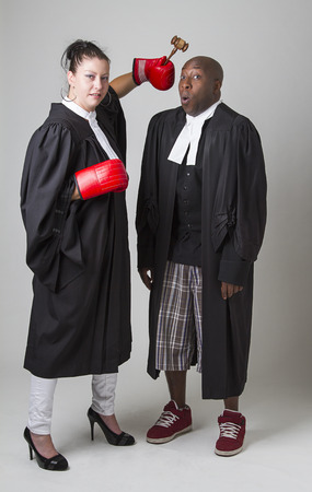 toga: woman hammering a man on the head with a gavel, both wearing canadian lawyers toga