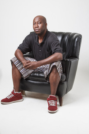 forty something: forty something bald black man, sitting in a black leather chair