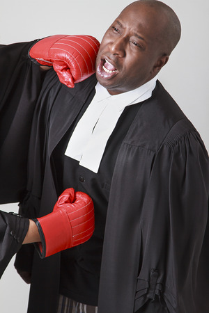 toga: bald black man wearing canadian lawyer toga getting punch in the face and in the guts by a red boxing gloves Stock Photo