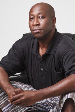 modelos negras: cuarenta algo que el hombre negro calvo, sentado en una silla de cuero negro