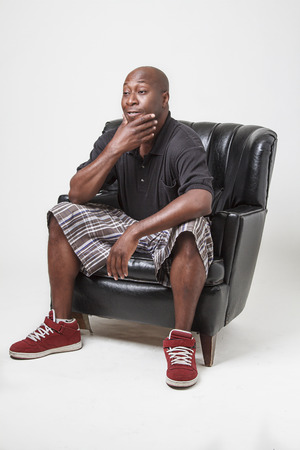 forty something: forty something bald black man, sitting in a black leather chair, holding his chin Stock Photo
