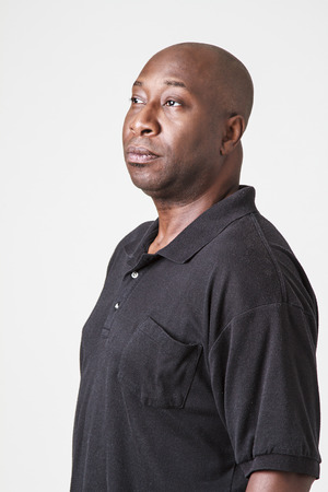 forties: black man in his forties, wearing a black polo, looking to the left