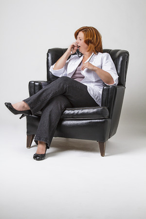 forty something: forty something woman with red hair, wearing a lab coat and sitting in a leather chair, in the middle of a yaw Stock Photo