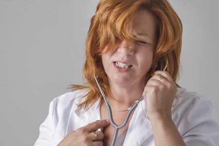 forty something: forty something woman with red hair, listening to her heart with a stethoscope with pain expression Stock Photo