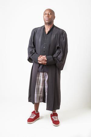 bald black man wearing a preacher toga, short and sneaker
