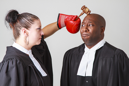 woman warrior: woman hammering a man on the head with a gavel, both wearing canadian lawyers toga
