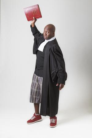 toga: hombre calvo negro en resumen y zapatilla de deporte, vistiendo una toga abogado canadiense, lanzando un libro de leyes roja en el suelo Foto de archivo