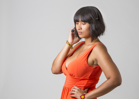 low cut: Young woman wearing low cut dress with headset Stock Photo