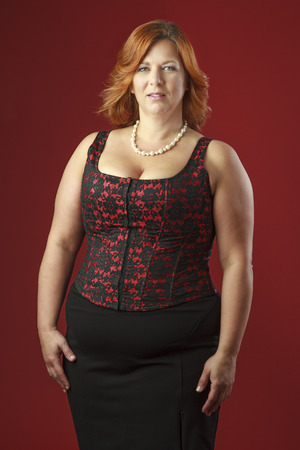 Woman in her fortie wearing a red corset Stock Photo