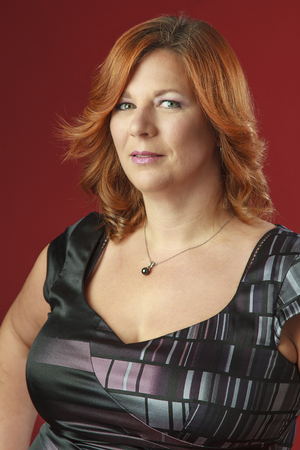 red hair woman in cocktail dress against a red background Standard-Bild