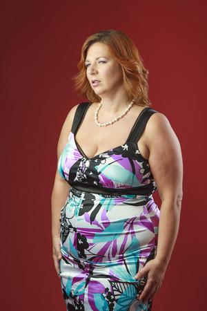 donne mature sexy: donna sensuale nella sua Fortie, che indossa un abito da cocktail colorato Archivio Fotografico