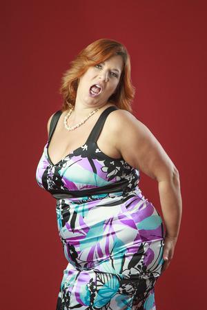 donne mature sexy: capelli rossi donna in cocktail colorato, schiaffi il suo culo con l'espressione sexy