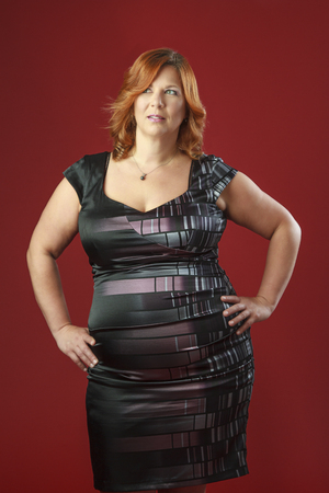 unhealthy thoughts: red hair woman, with her hand on her hips, wearing a cocktail dress against a red background