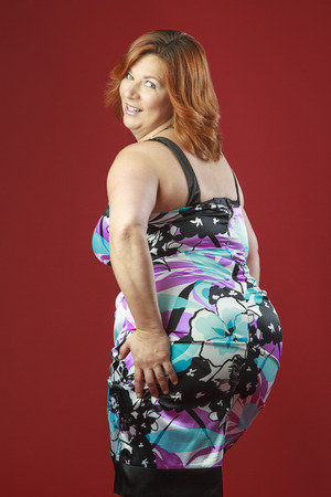 fat women: Woman in her fortie, wearing a colorful cocktail dress, showing her butt with a great big smile Stock Photo