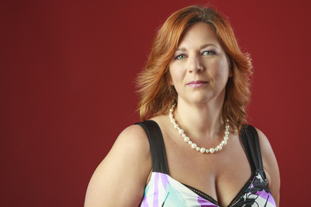 forty year old woman with red hair against a red background