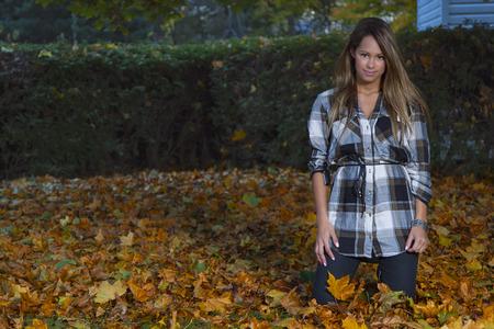 mujer arrodillada: Mujer joven que se arrodilla en hojas muertas