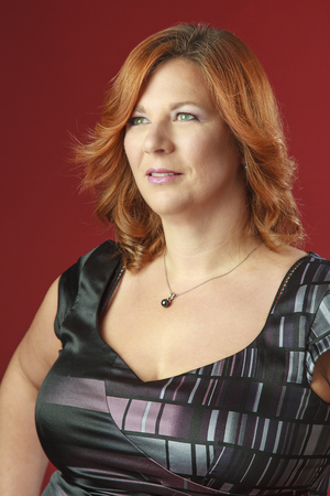 forties: Portrait of a woman in her forties, with red hair, against a red background