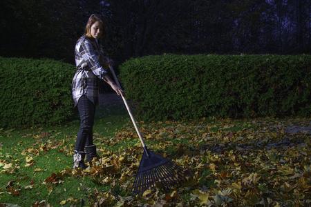 twenties: young woman in her twenties, raking leaves