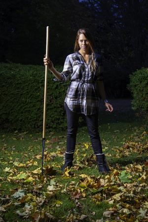 twenty something: twenty something girl holding a rake at night Stock Photo