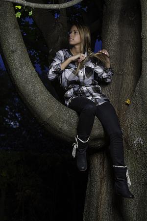 twenty something: twenty something girl sitting on a tree branch tying her hair