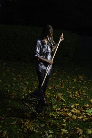 twenties: young woman in her twenties, raking leaves at night