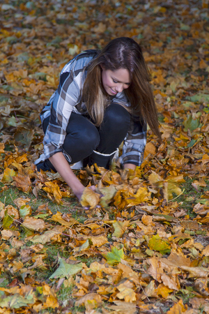 dode bladeren: young woman picking up dead leaves
