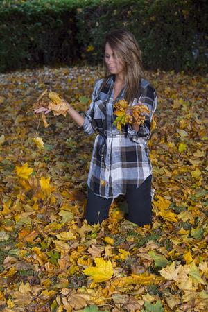 mujer rodillas: Joven mujer de rodillas en las hojas muertas y jugar en ellas