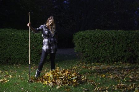 twenty something: twenty something girl holding a rake and looking at a small pile of leaves