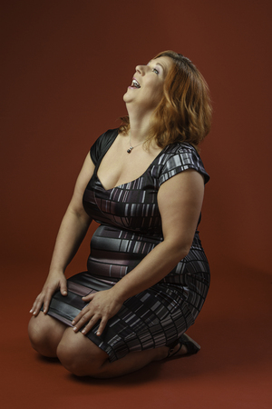 head back: Woman in her forty sitting on her knees laughing with her head back Stock Photo